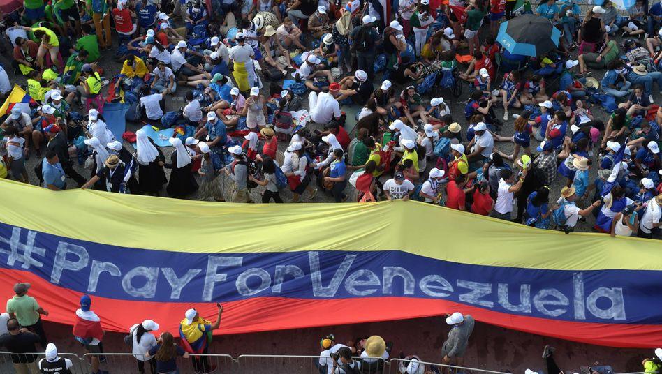 Pilger halten in Panama eine Flagge für Venezuela