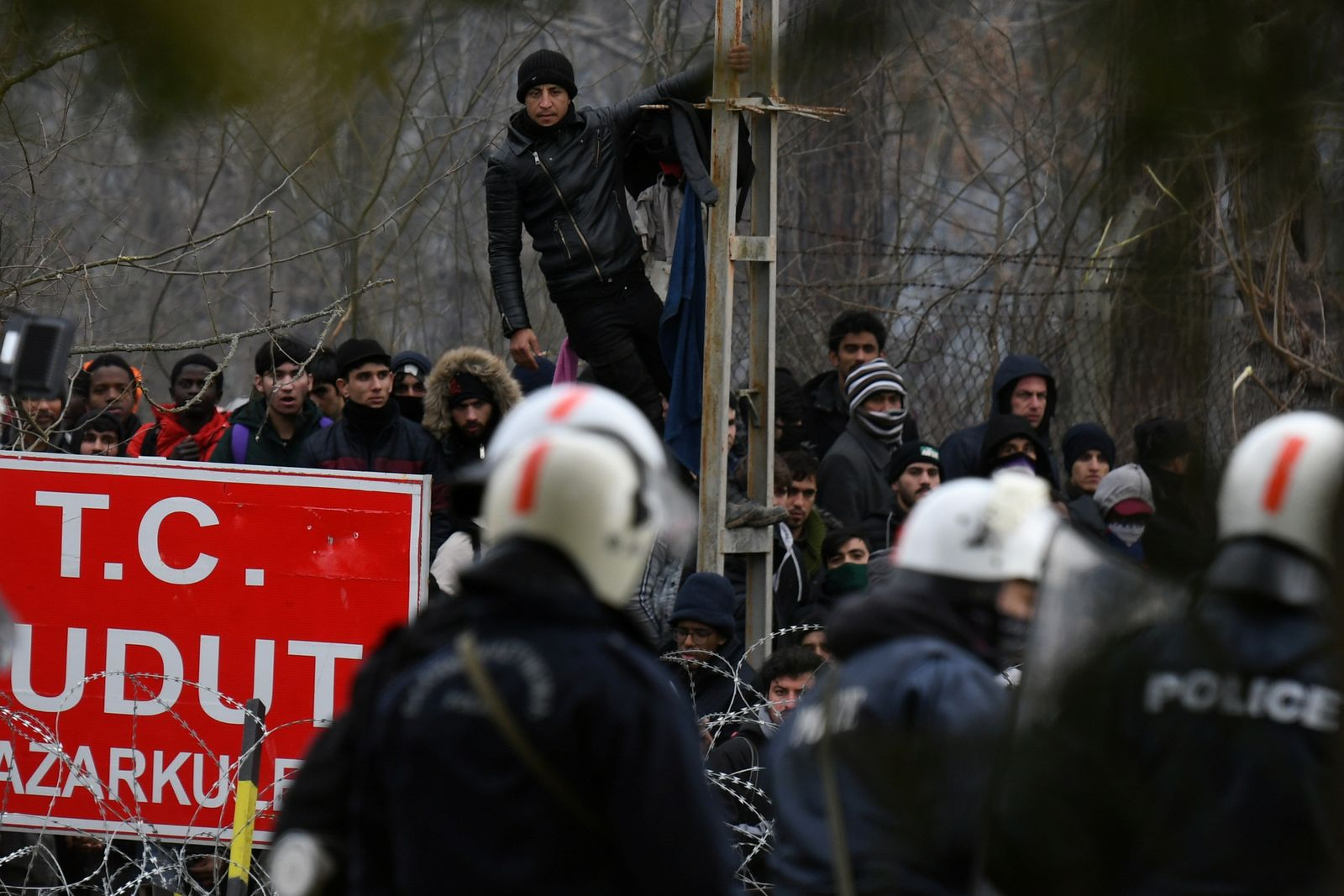 Migrants who want to cross into Greece from Turkey are gathered at the borderline as Greek riot police stand guard at the closed Kastanies border crossing with Turkey's Pazarkule, in the region of Evros