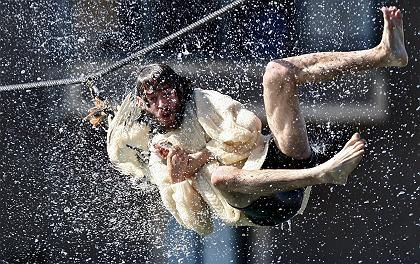 """A man hangs from a goose""""s neck during the """"Antzar Eguna,"""" the Day of the Goose, last September."""