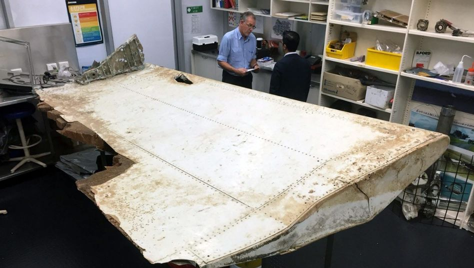 Investigators examine a piece of aircraft debris believed to be an outboard wing flap belonging to Malaysia Airlines Flight MH370.