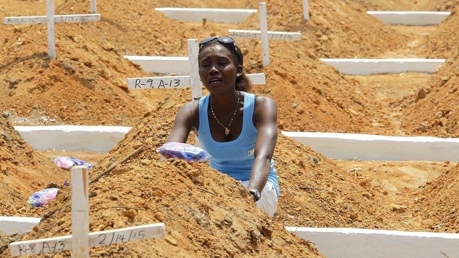 Ebola-Massengrab in Liberia: Eine Angehörige weint um einen Verstorbenen