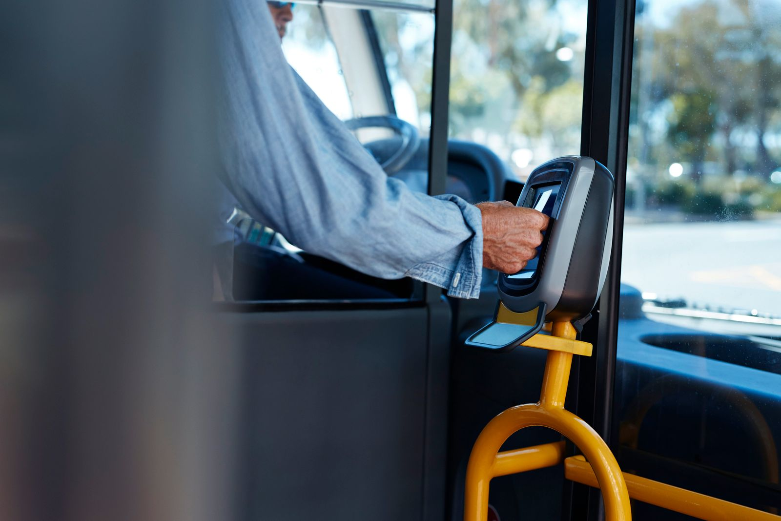Mature man using travel card to pay for public bus ride