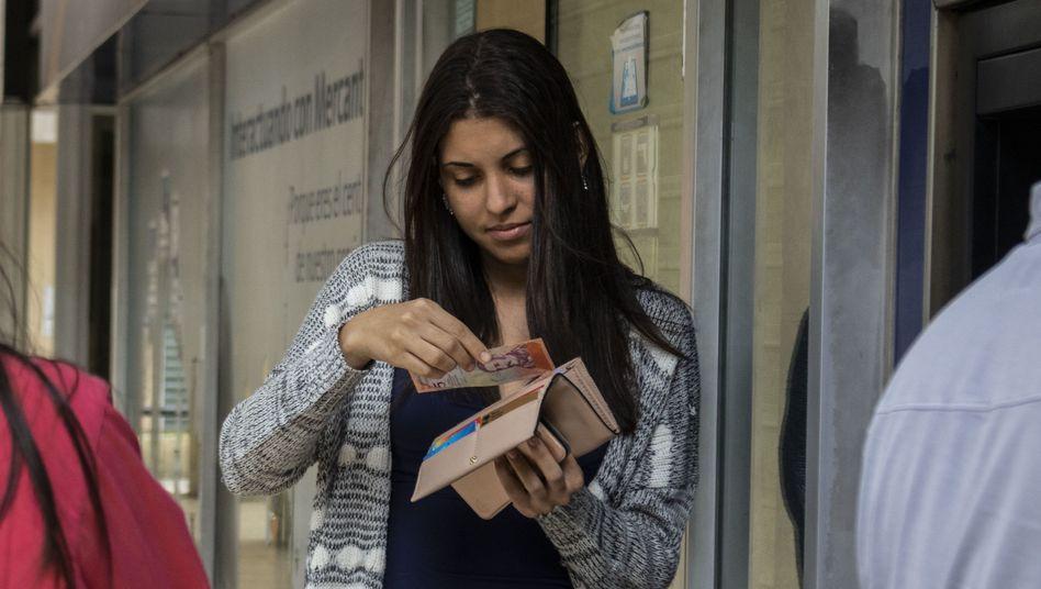 Frau in Caracas betrachtet Venezuelas neue Banknoten