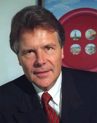 Sparsamer Investor Wöhrl vor dem Knopf-Logo seiner Firma: Zurück im Fluggeschäft