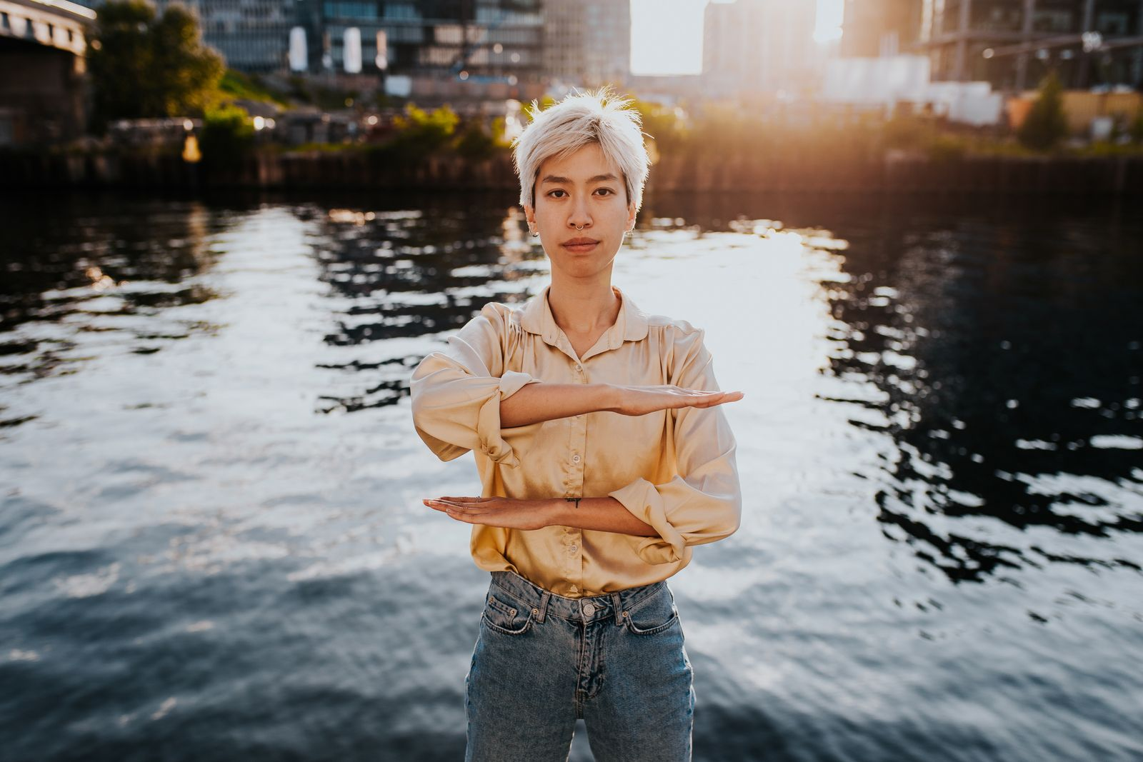 Portrait Of Young Woman Gesturing Equal Sign While Standing Against Lake In City