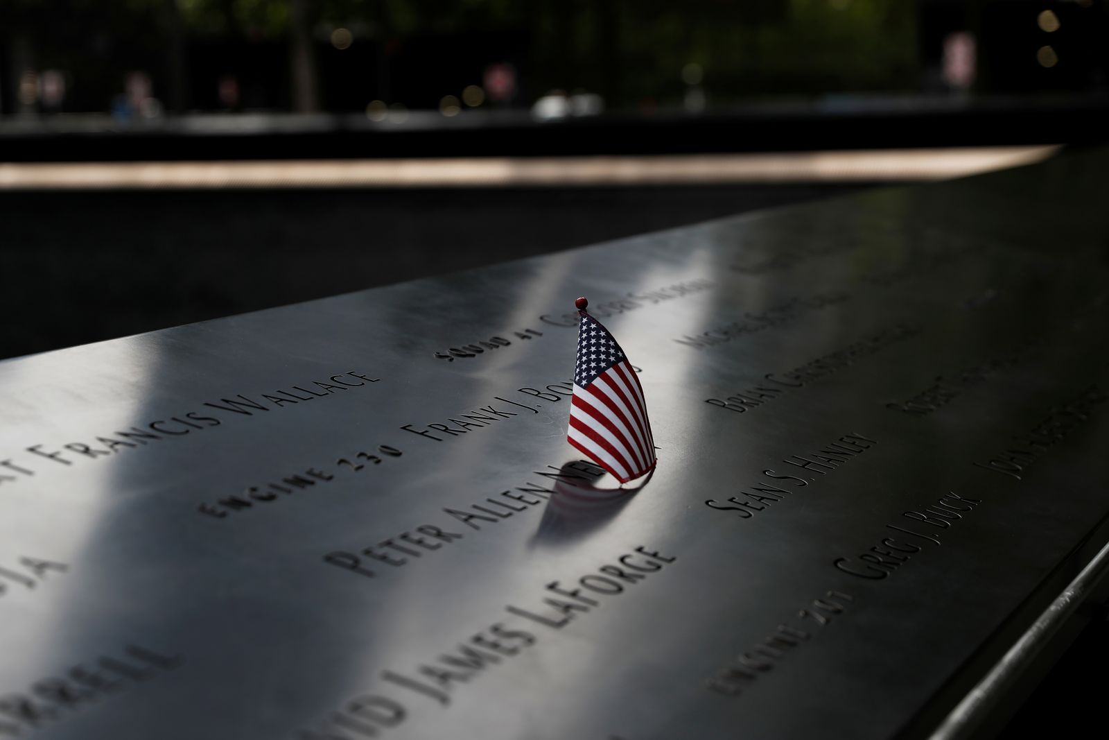 A U.S. flag is placed on one of the victims' names at the south reflecting pool of the National 9/11 Memorial, two days before the 19th anniversary of attacks, amid the coronavirus disease (COVID-19) pandemic, in the lower section Manhattan, New York City