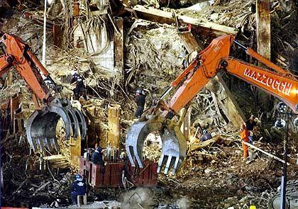 """Mit mächtigen Greifarmen durchwühlen Bagger die Trümmer des WTC-Turmes """"Tower One""""."""
