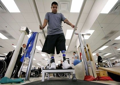 A soldier undergoes therapy with both of his artificial legs at Walter Reed Army Medical Center in Washington, DC.