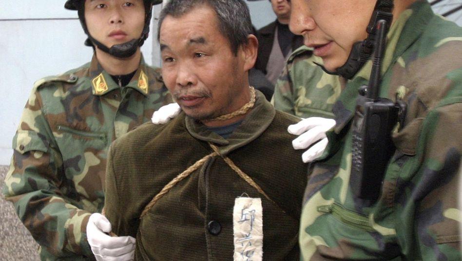 Chinesische Polizisten mit Todeskandidat (im Jahr 2006): Anpassung an internationale ethische Standards