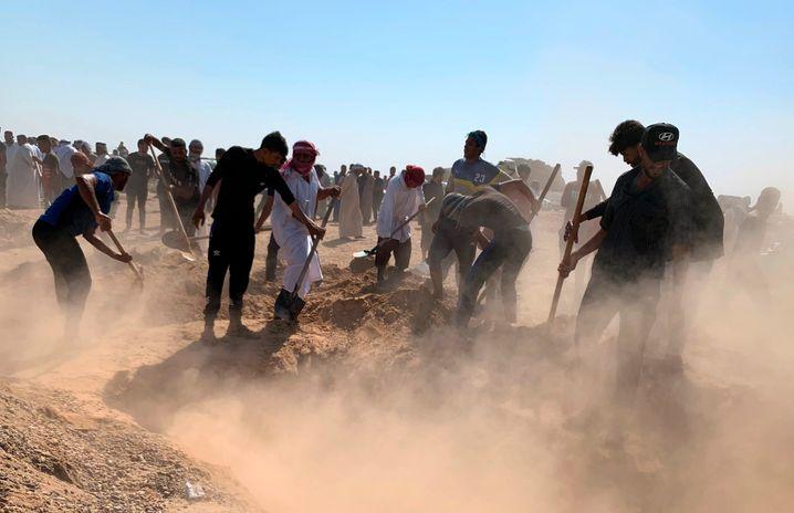 Männer heben ein Grab für 12 Iraker aus, die wenige Tage nach einer Entführung erschossen aufgefunden wurden