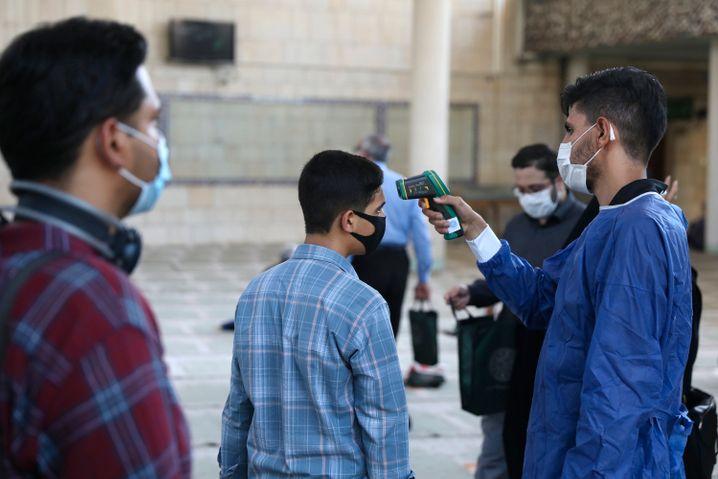 Beim Betreten einer Teheraner Moschee wird bei einem Gläubigen die Temperatur gemessen. Das Foto entstand am 30. Juli
