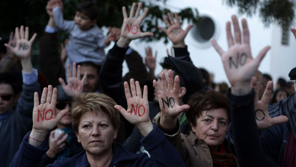 """Cypriots show their palms reading """"No"""" during a protest against an EU bailout deal outside the parliament in Nicosia on Monday."""