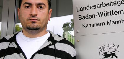 Garbage collector Mehmet G. stands outside the court in Mannheim that found that he should not have been fired for taking home garbage.