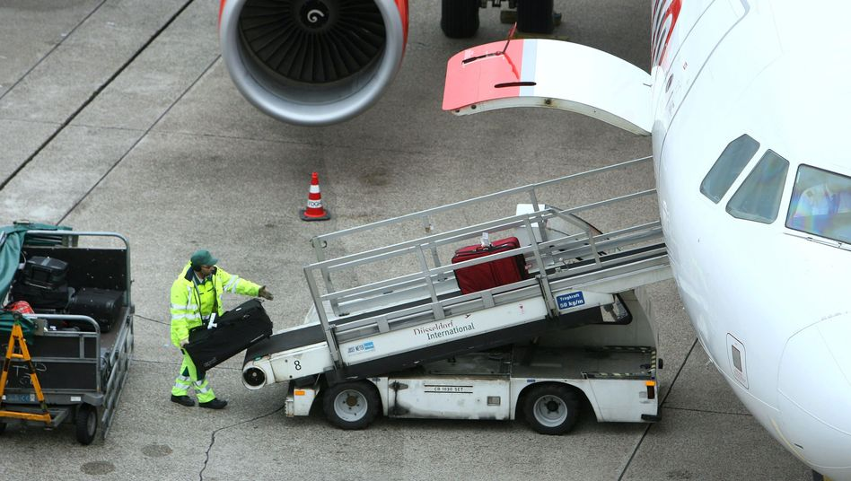 Workers at the Düsseldorf Airport load baggage onto an Air Berlin plane.