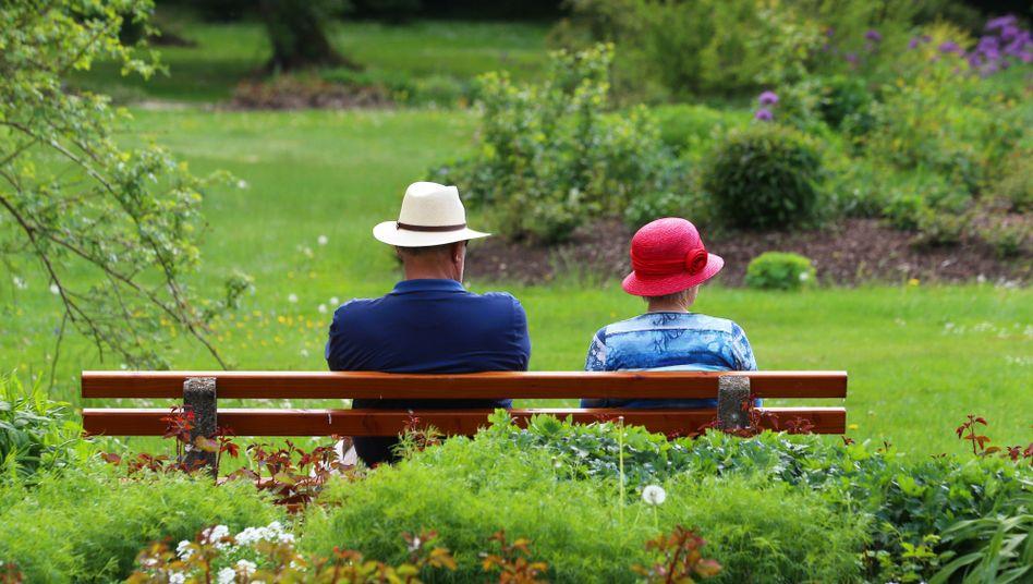 Ein Mann und eine Frau sitzen auf einer Bank im frühlingshaften Kurpark von Bad Wörishofen in Bayern