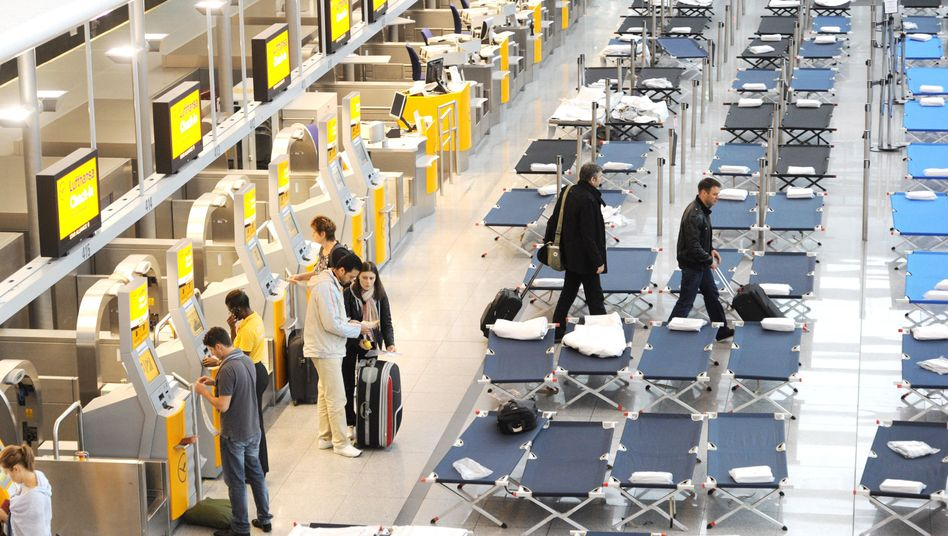 Lufthansa passengers check in for flights in Munich amid cots set up for those stranded by the cabin crew strike.