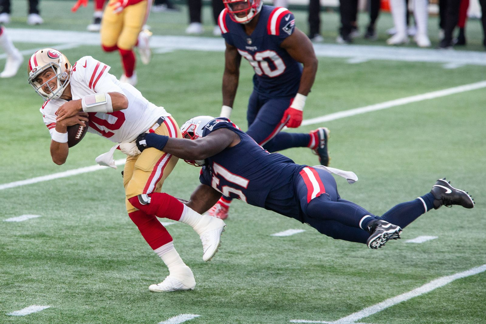 San Francisco 49ers quarterback Jimmy Garoppolo (10) is pulled down by New England Patriots linebacker Ja Whaun Bentley