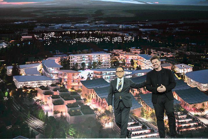 """Toyota-Chef Akio Toyoda mit Architekt Bjarke Ingel vor einer Darstellung der """"Woven City"""""""