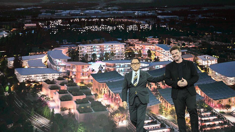 """Toyota-CEO Akio Toyoda (l.) und Architekt Bjarke Ingel vor einer Darstellung der """"Woven City"""""""