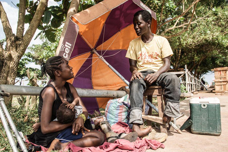 Patrick Koroma mit seiner Frau Mussu Fofanah und dem gemeinsamen Baby. Fofanah verkauft auf der Straße Wasser und Softdrinks, während er mit seinem dreirädrigen Keke Kunden durch Freetown chauffiert.