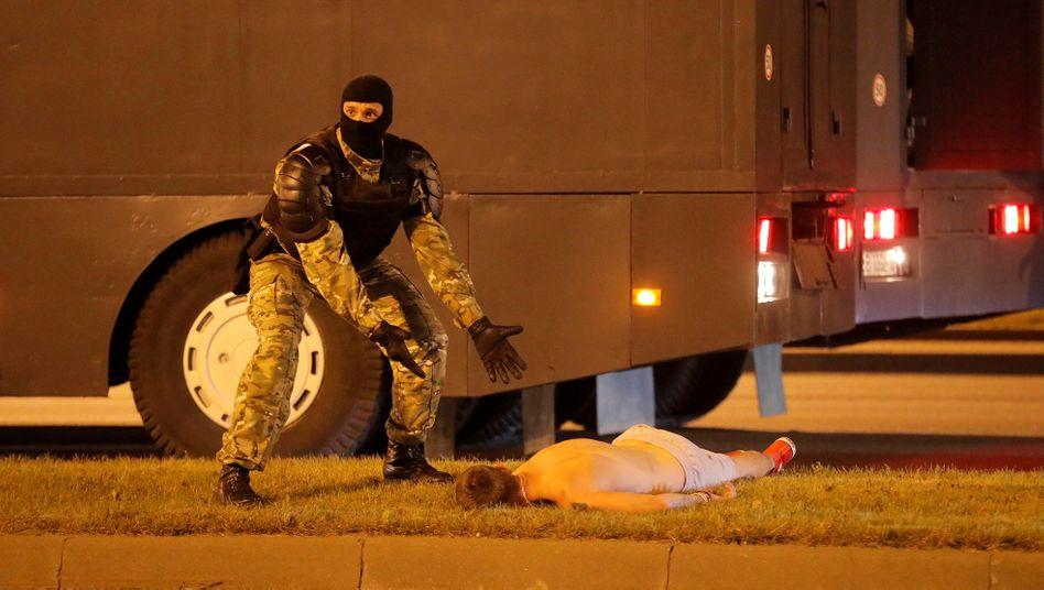 Szene aus Minsk: Ein Vertreter der Sicherheitskräfte neben einem Demonstrationsteilnehmer