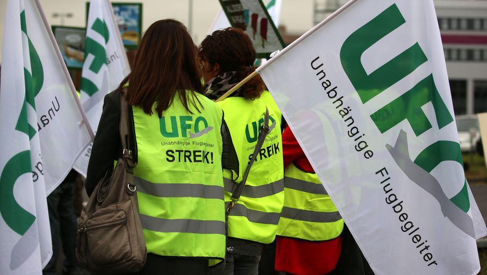 Streikende Flugbegleiter mit Fahnen der Gewerkschaft UFO (Unabhängige Flugbegleiter Organisation)