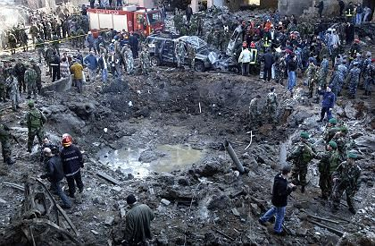 Workers and soldiers stand around a massive crater after a bomb attack that tore through the motorcade of former Prime Minister Rafik Hariri in Beirut, Lebanon, on Feb. 14.