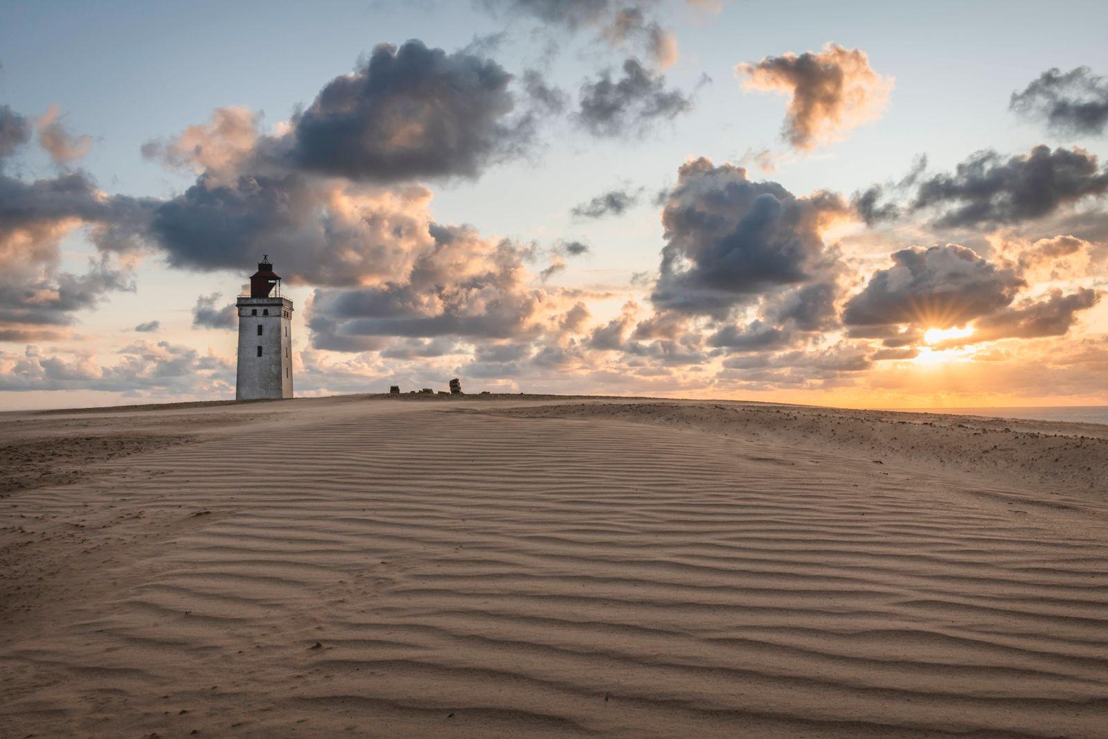Denmark, Lonstrup, Clouds over rippled sand dunes and Rubjerg Knude Lighthouse at sunset PUBLICATIONxINxGERxSUIxAUTxHUNx
