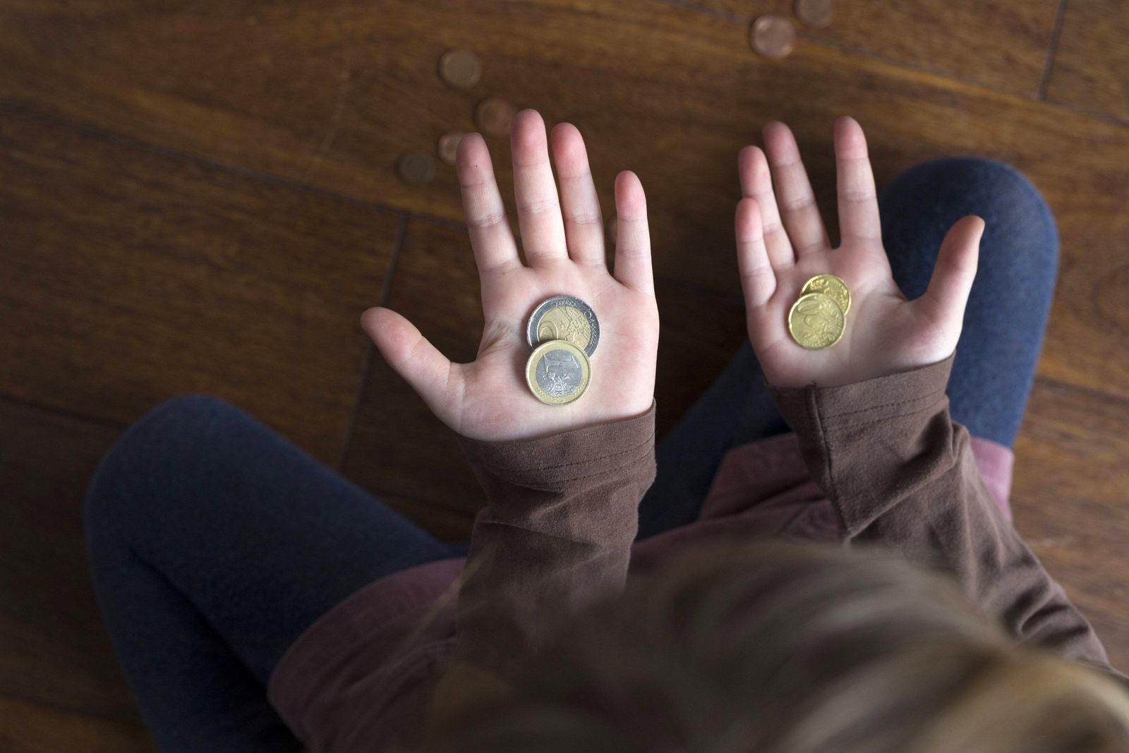 Symbolfoto zum Thema Kinderarmut und Kindergrundsicherung Fuenfjahriges Maedchen zaehlt ihr Taschen