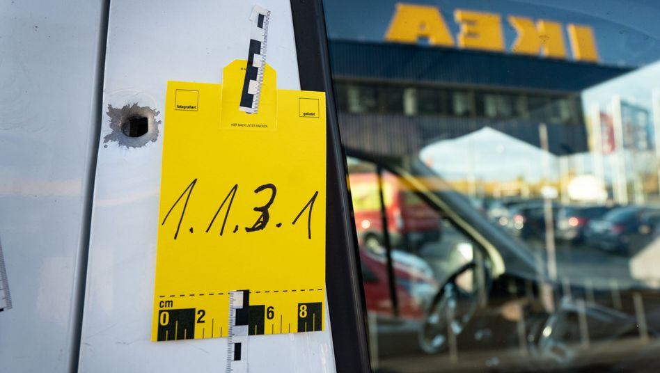 Fahrzeug mit Einschussloch vor dem Ikea-Möbelhaus im Frankfurter Stadtteil Nieder-Eschbach: Geldbote schwer verletzt