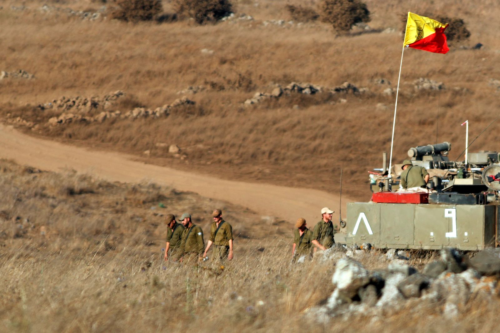 Israeli soldiers walk next to a tank in the Israeli-controlled Golan Heights near the Israel-Syria frontier