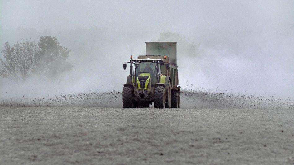 Traktor beim Miststreuen