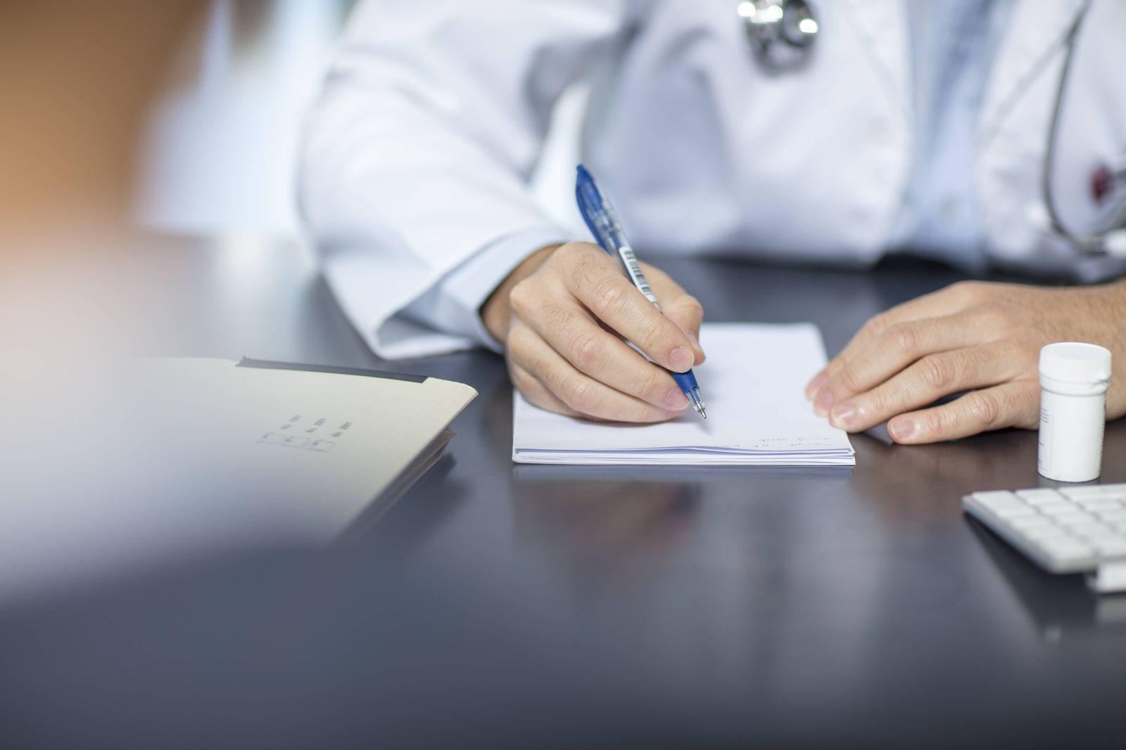 Doctor sitting at his desk taking notes model released Symbolfoto property released PUBLICATIONxINxG