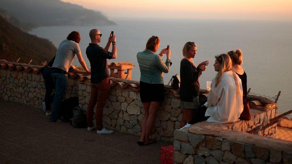 Touristen an einem Aussichtspunkt mit Blick auf das Mittelmeer in Palma de Mallorca