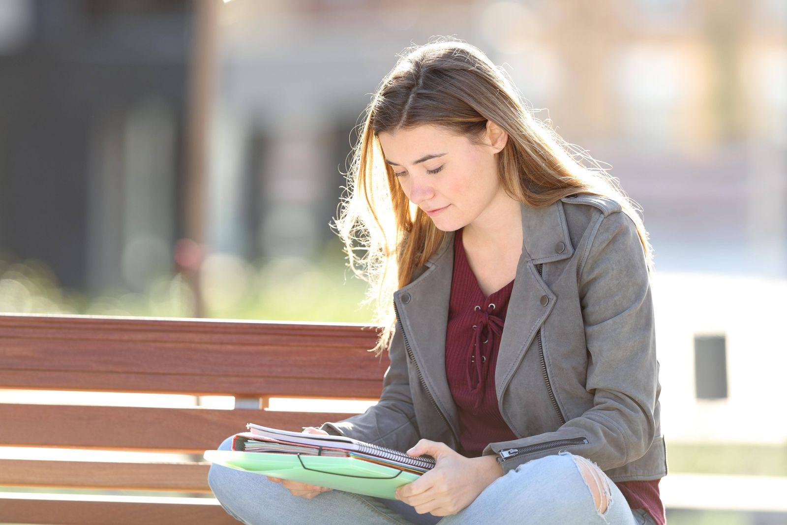 Student learning reading notes on a bench model released Symbolfoto PUBLICATIONxINxGERxSUIxAUTxON