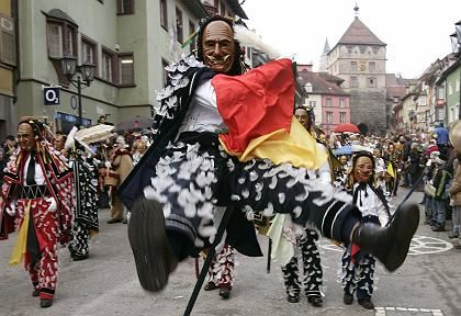 "A carnival reveller vaults on his pole during the ""Narrensprung"" carnival parade in Rottweil."