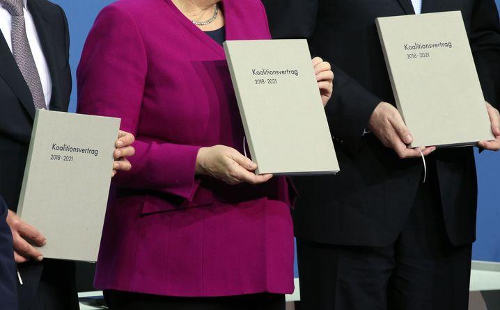 Angela Merkel, Horst Seehofer und Olaf Scholz mit dem Koalitionsvertrag