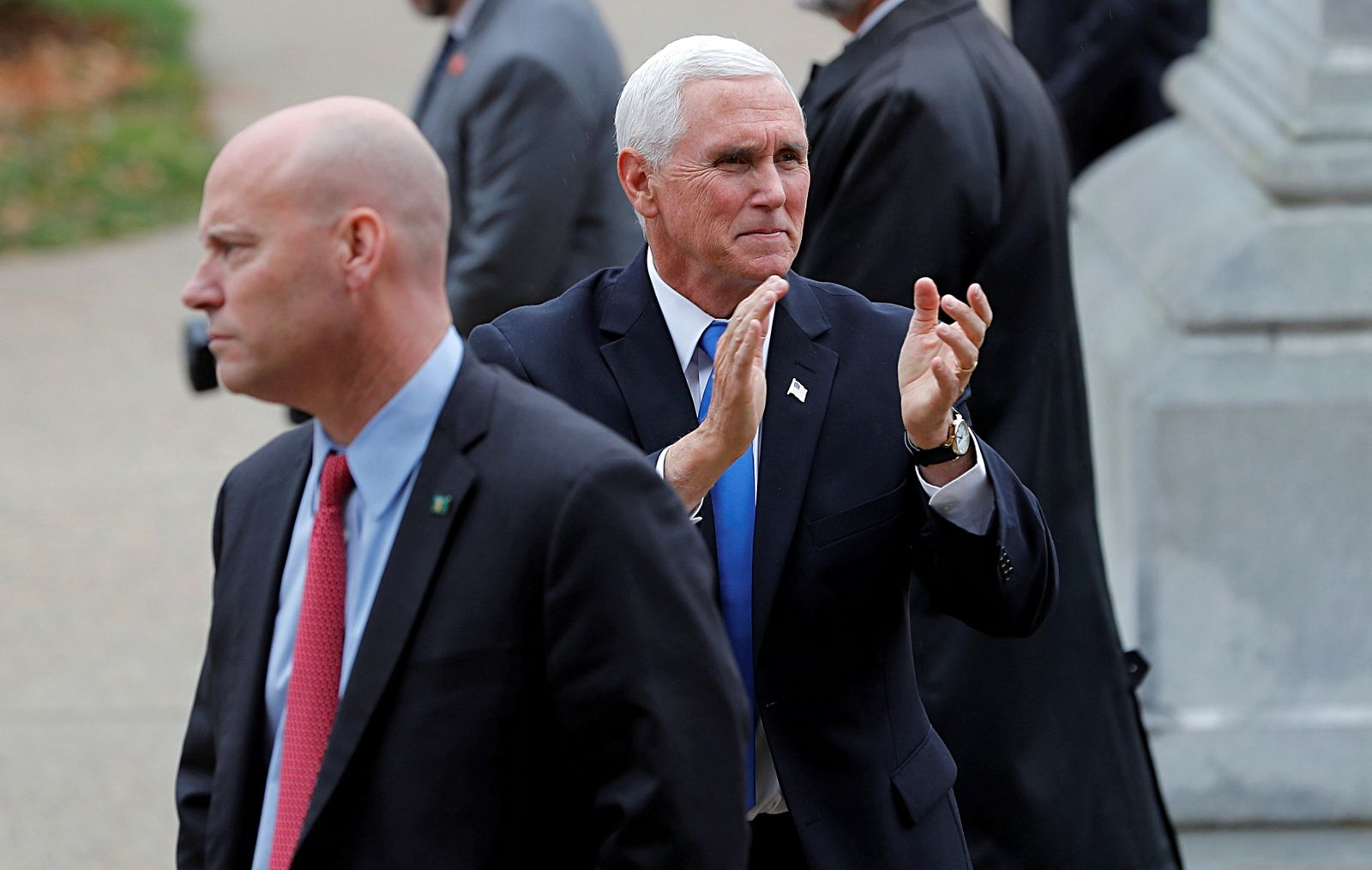 U.S. Vice President Pence reacts to supporters outside the New Hampshire State House as he walks near his Chief of Staff Marc Short in Concord
