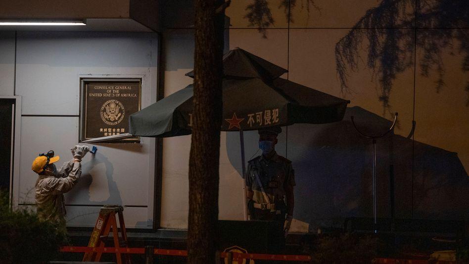 In der Nacht zum Montag hebelt ein Arbeiter das Eingangsschild des US-Konsulats in Chengdu in der Provinz Sichuan aus der Wand