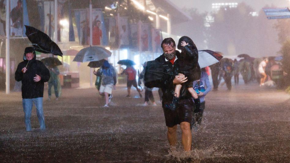 Zuschauer der US Open wurden von dem Starkregen überrascht – und waten auf den überfluteten Wegen vor dem Stadion