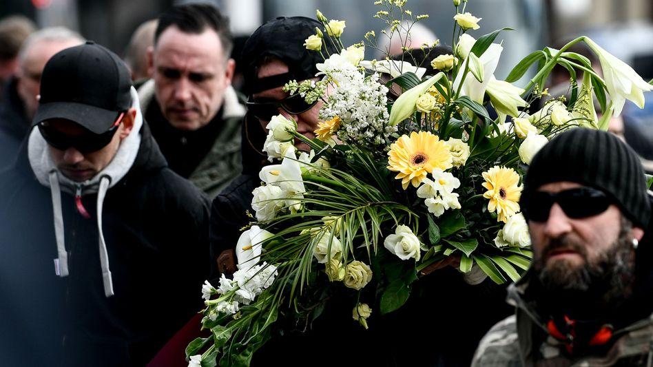 Hooligans bei Trauermarsch: Helle Blumen vor braunem Hintergrund