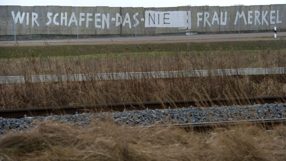 """""""We'll Never Manage It, Ms. Merkel,"""" reads graffiti painted along a wall on a road on Rügen Island in northeastern Germany."""