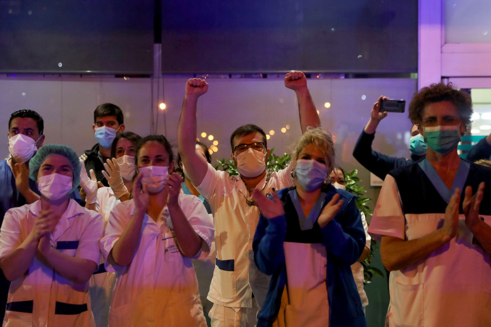 Medical staff from the Fundacion Jimenez Diaz hospital applaud as neighbours applaud from their balconies in support for healthcare workers, during the coronavirus disease (COVID-19) outbreak, in Madrid