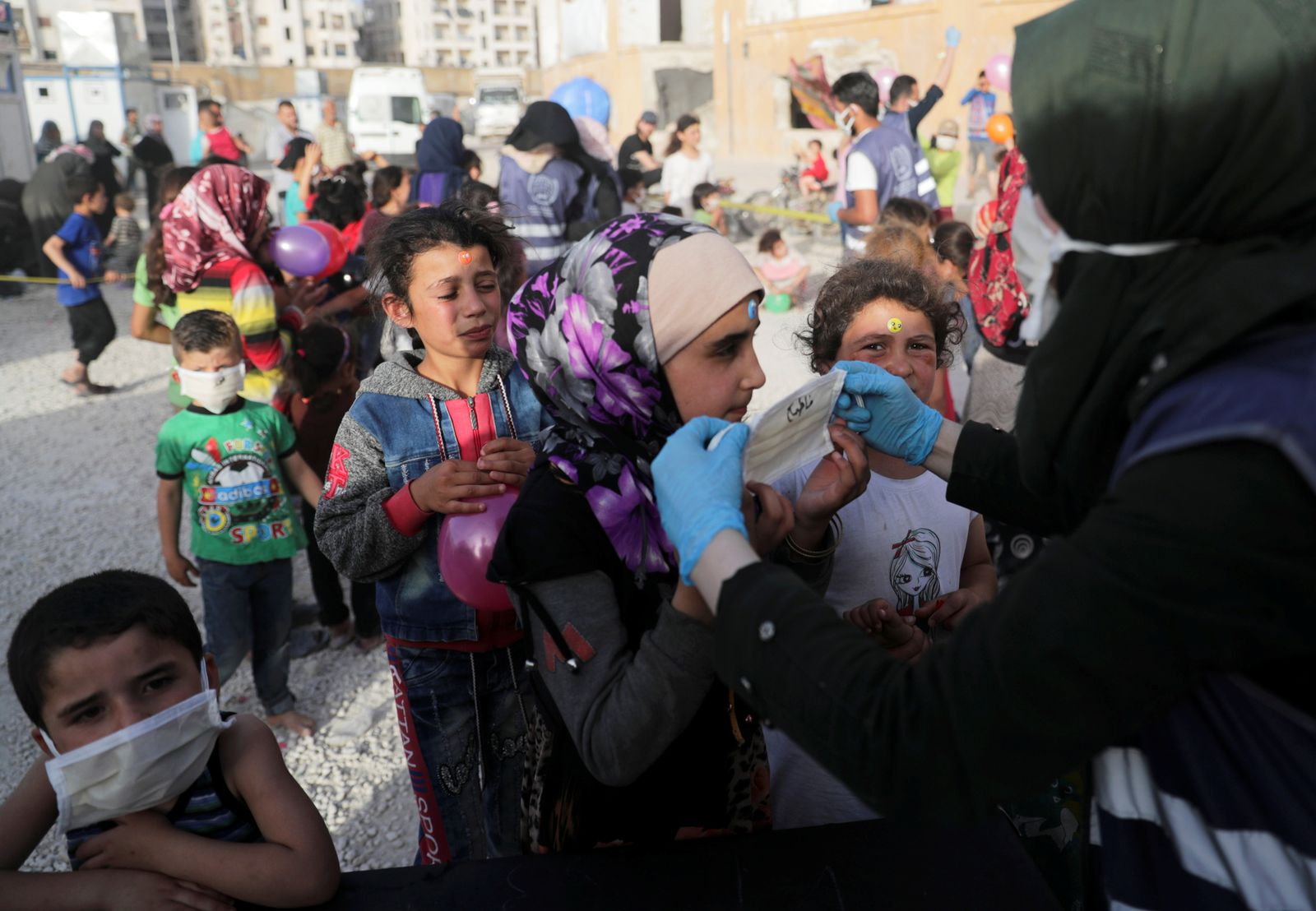 A volunteer distributes face masks to internally displaced children, amid concerns over the spread of the coronavirus disease (COVID-19), at an IDP camp in Idlib