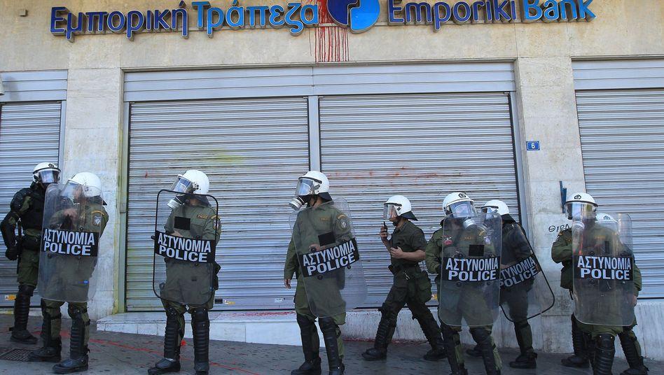 Polizisten vor griechischer Bank: Das Risiko trägt mitlerweile vor allem der Staat