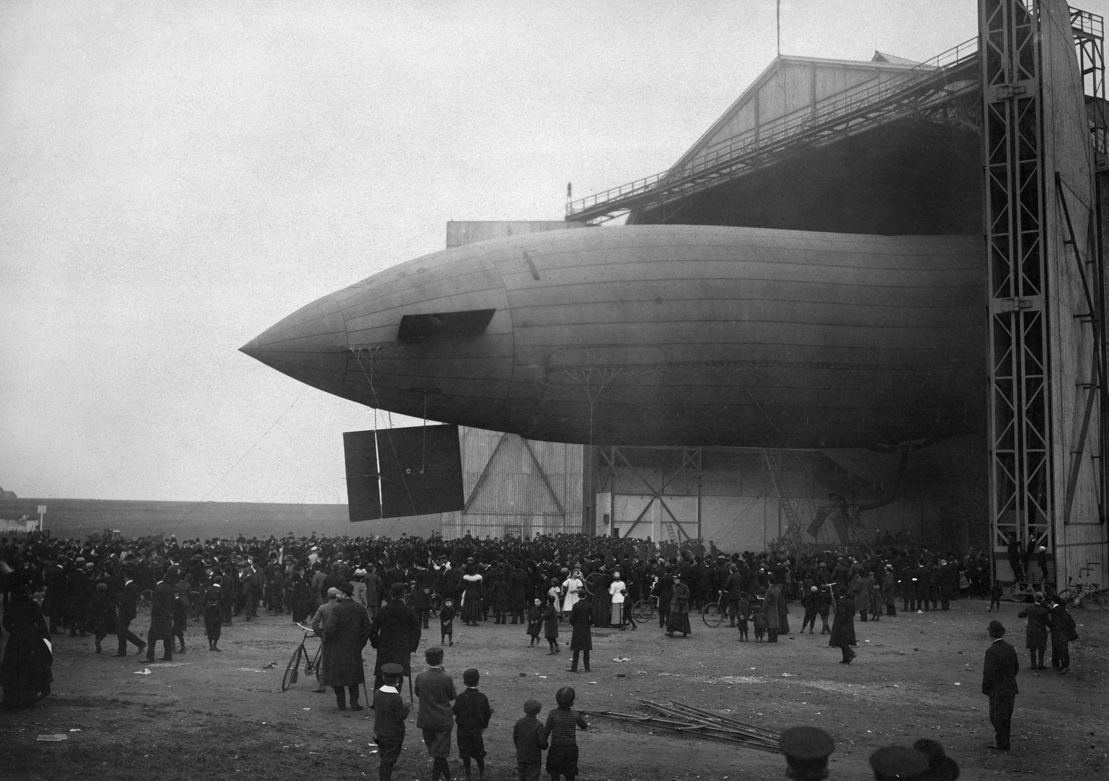 Luftschiff 'Parseval' PL1, Jungfernfahrt am 21.September 1909: Schaulustige begleiten das Luftschiff beim Verlassen des Hangars.