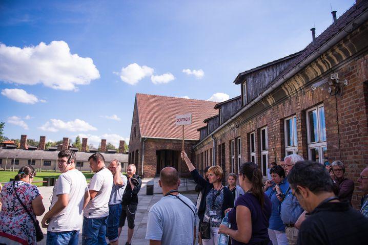 Führung der deutschen Gruppe durchs Konzentrationslager Auschwitz: Die Geschichte tragen