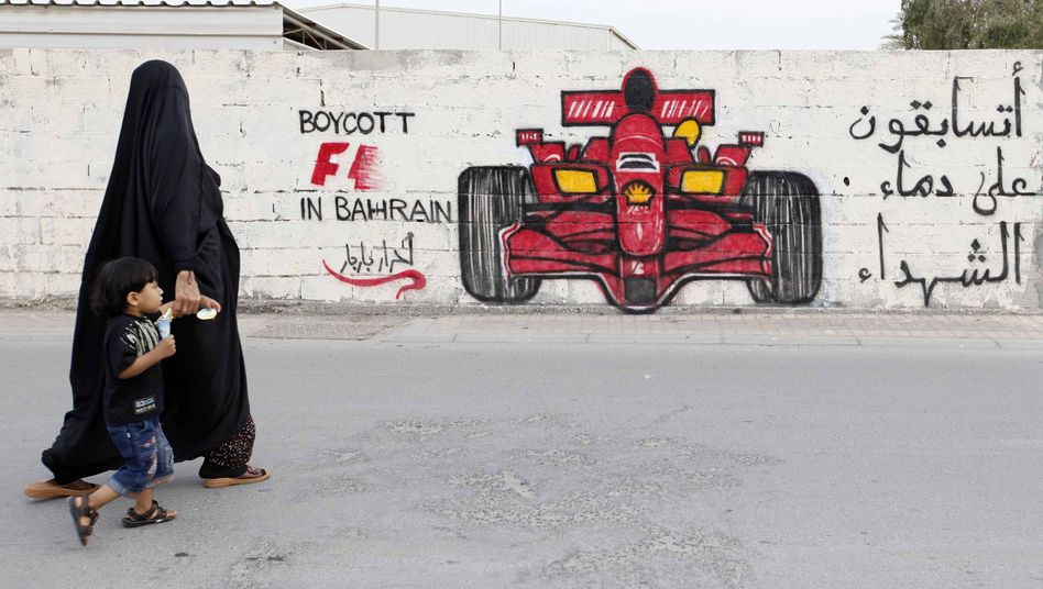 A woman and her child pass in front of anti-Formula One graffiti in the village of Barbar, Bahrain.