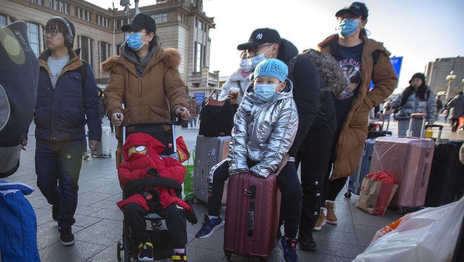 Reisende am Pekinger Bahnhof: Viele tragen einen Mundschutz, um sich vor dem neuartigen Coronavirus zu schützen