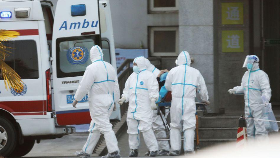 Patienten werden in ein Krankenhaus in Wuhan gebracht: In der Stadt wurden die ersten Fälle gemeldet